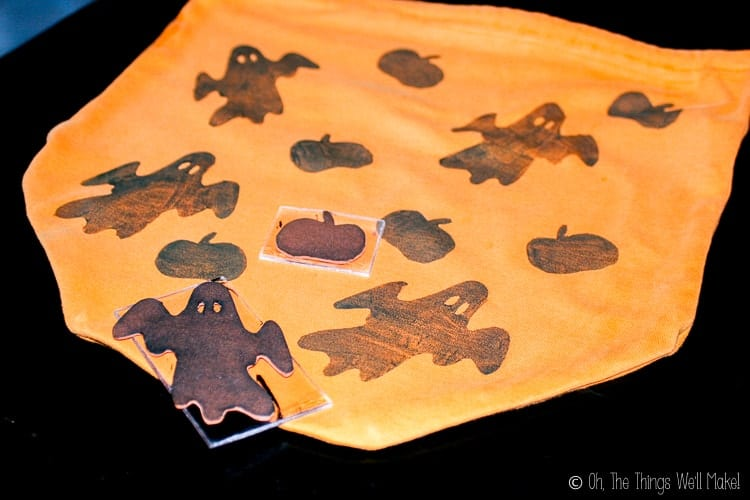 stamping ghost and pumpkin shapes onto our homemade trick-or-treat bag with homemade fabric stamps