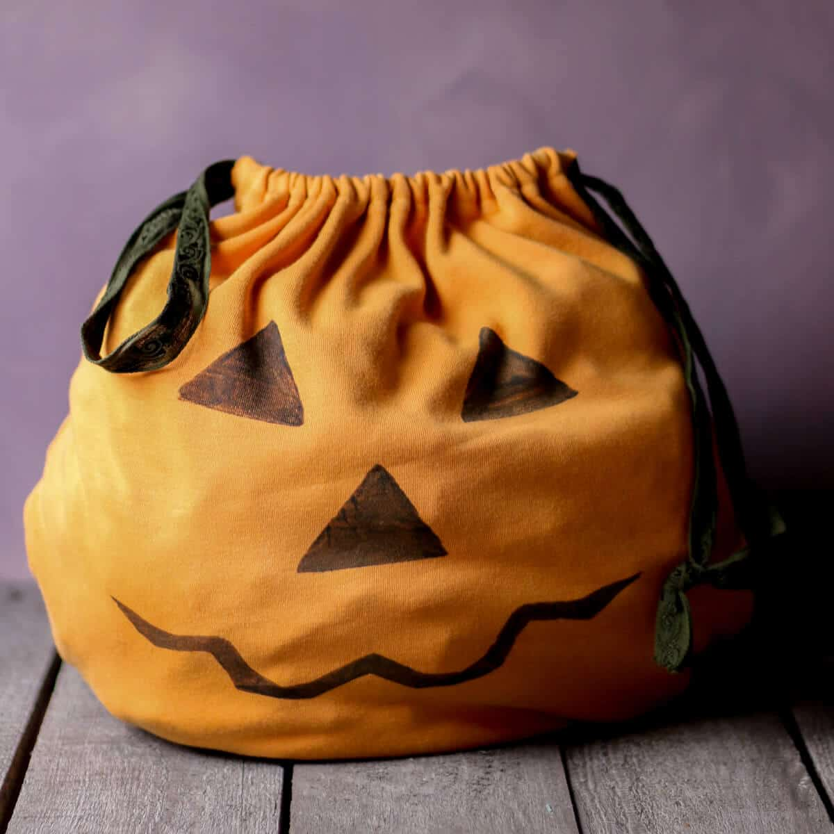 An orange homemade trick-or-treat bag decorated with a Jack-o-lantern face.