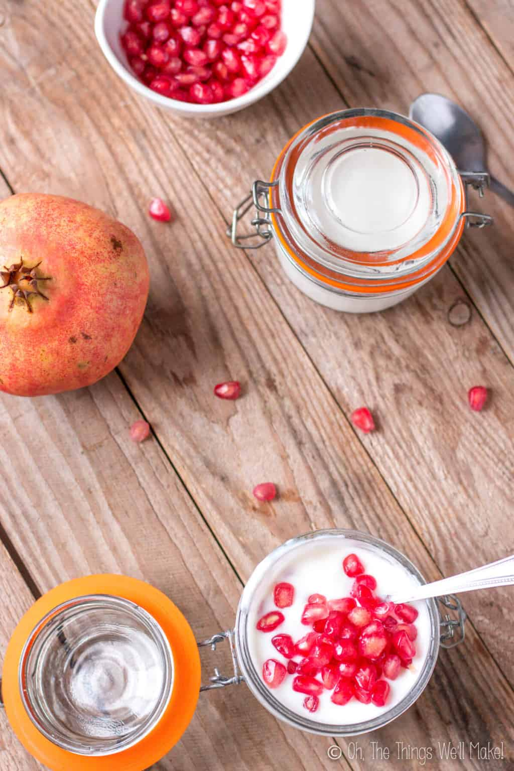 Overhead view of two jars of homemade yogurt on a wood surface. Bottom jar is open and has a spoon inside it with fresh pomegranate topping it. Top jar is closed and is beside a pomegranate fruit and a bowl full of pomegranate seeds.