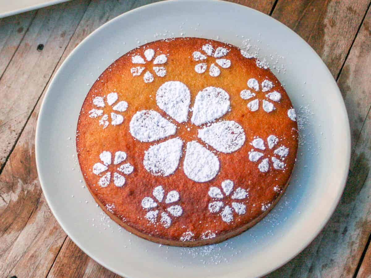 Overhead view of a golden brown circle spanish almond cake decorated with powdered sugar in floral shapes.