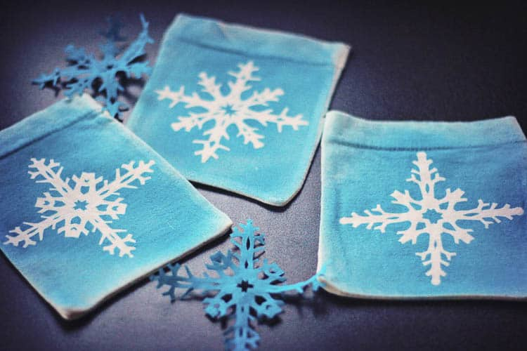 Save the waste of wrapping paper by using beautiful reusable gift pouches.Learn how to paint a snowflake Christmas gift pouch made from recycled t-shirt sleeves. This is a fun craft for both adults and kids.