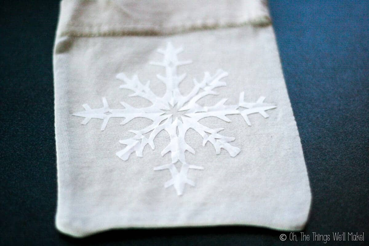 A cloth pouch with a freezer paper snowflake ironed on the front.
