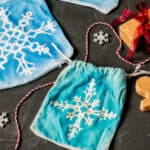 Two homemade blue cloth gift pouches with painted snowflakes designs and embellished with rhinestones.