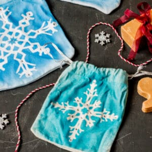 two homemade gift pouches with snowflakes painted on them and embellished with rhinestones.