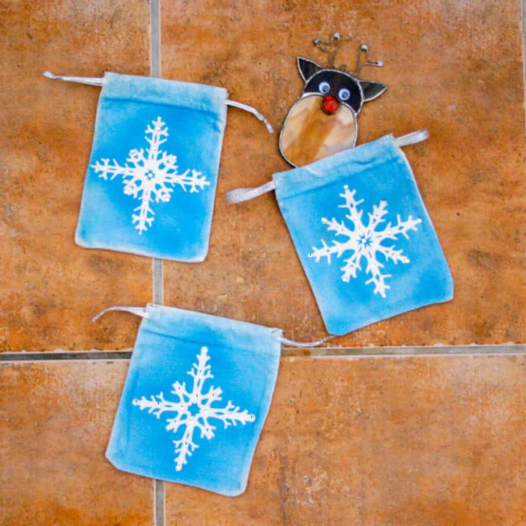 3 snowflake pouches with a homemade stained glass reindeer ornament