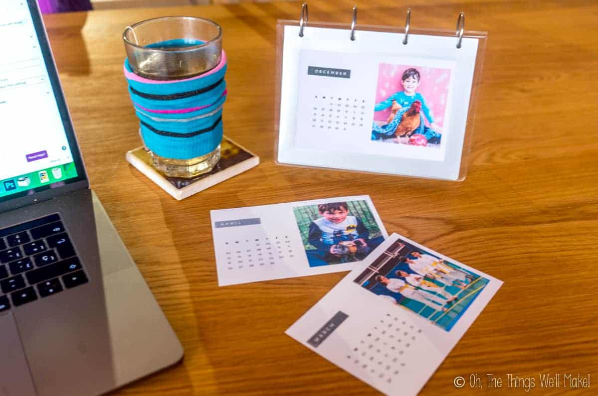 A homemade photo calendar next to a computer and a glass full of tea covered in a blue sock cozy.