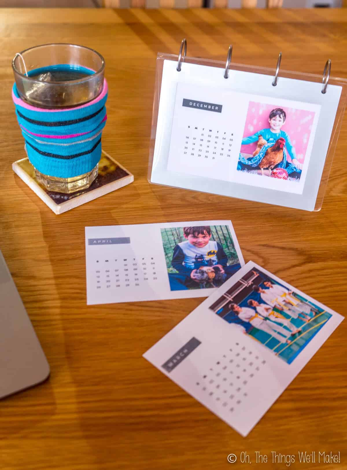 A homemade photo calendar in a flip frame next to a computer and a glass full of tea and some extra printed out photo calendars.