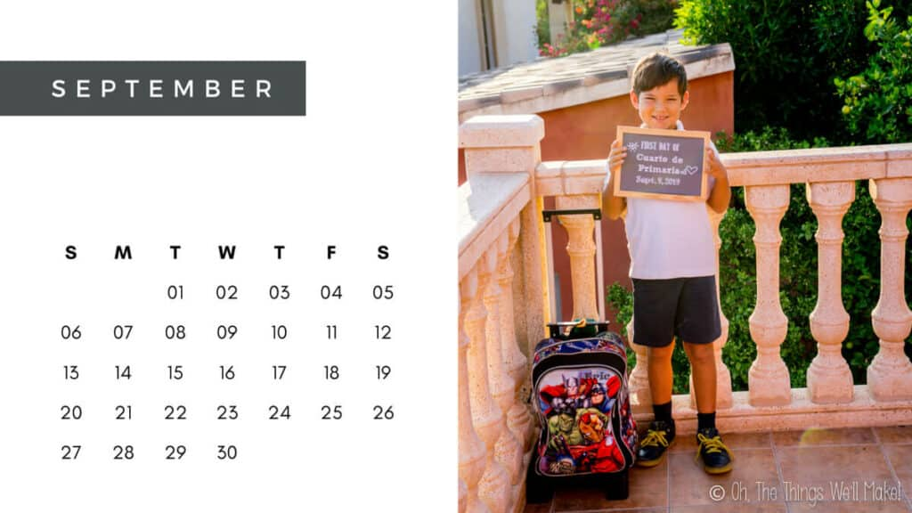 A September calendar with a photo of a boy holding a sign announcing the first day of school