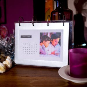 A homemade photo calendar sitting on a mantle with some candles and other trinkets.