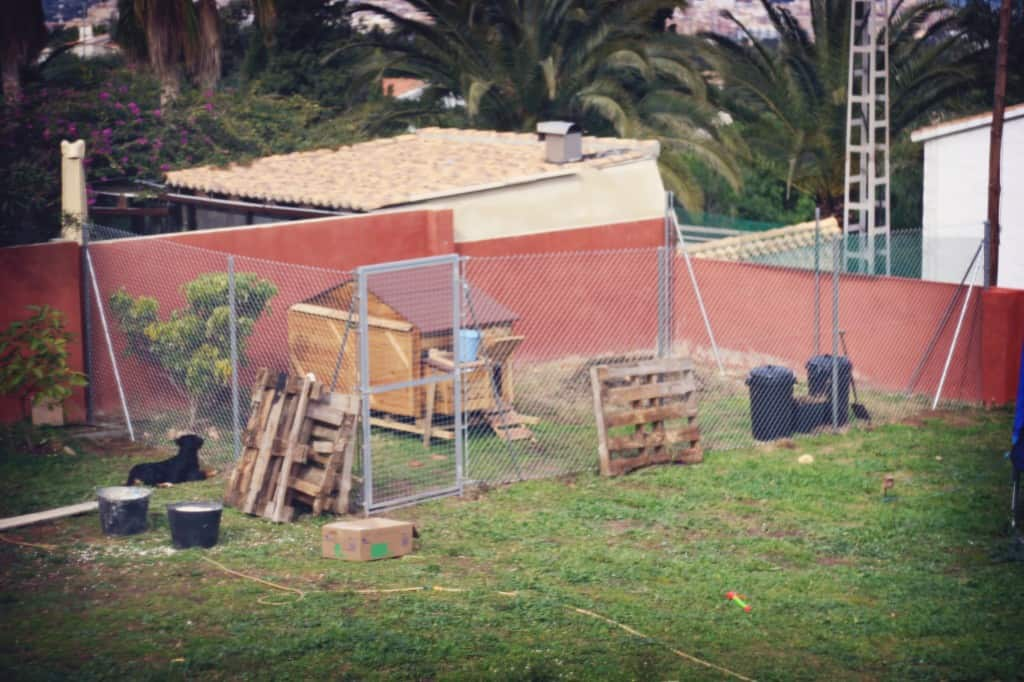 A chicken coop surrounded by a 2m high chain link fence.