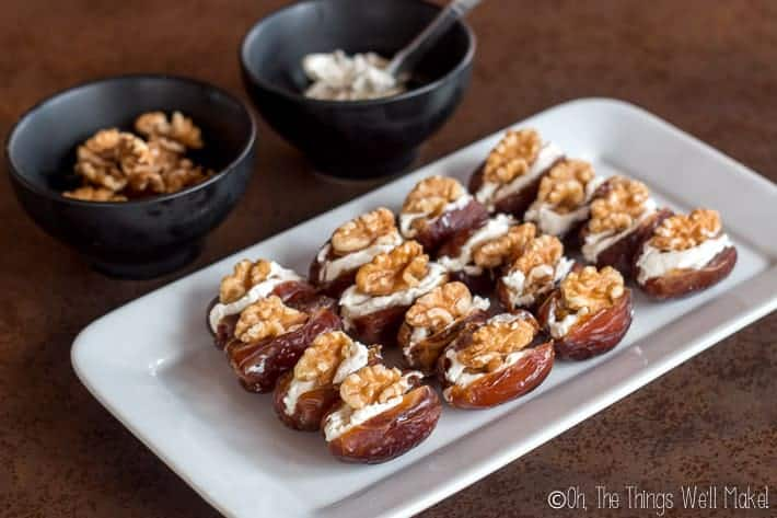 An appetizer platter of cream cheese stuffed dates with wlanuts