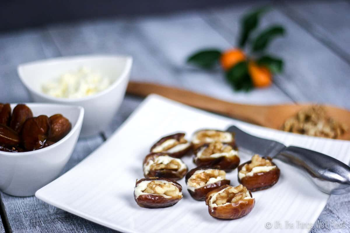 Close up of eight dates stuffed with cream cheese and topped with walnuts on a plate.