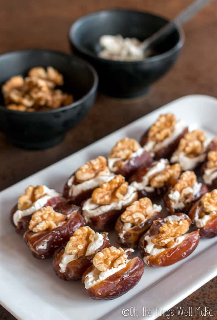 16 stuffed dates on a white platter in front of halved walnuts and a bowl of cream cheese
