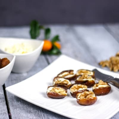 A white square plate on the right full of dates stuffed with cream cheese and walnuts, with two bowls on the left side full of dates and cream cheese.