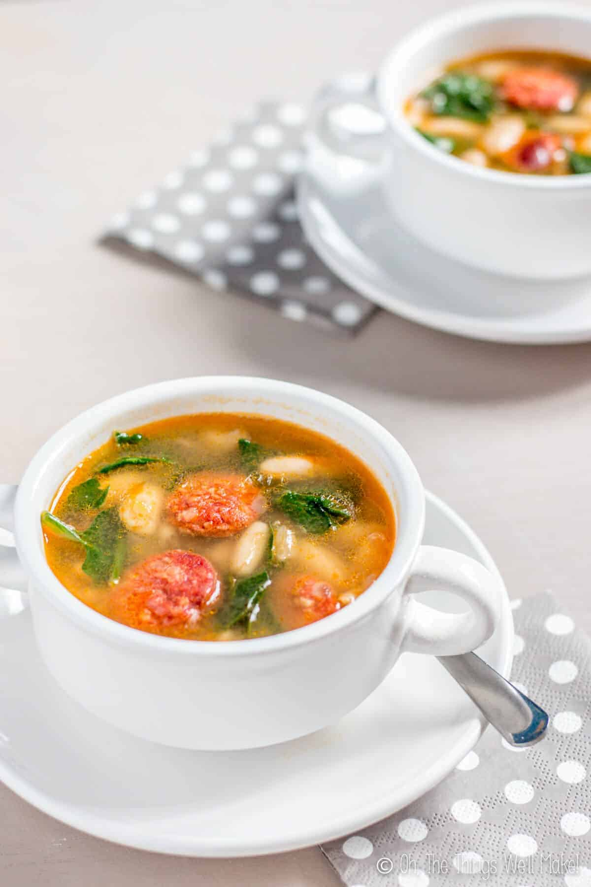 Two bowls of white bean and chorizo soup with spinach