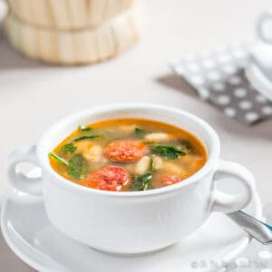 An overhead view of a bowl of white bean and chorizo soup with spinach