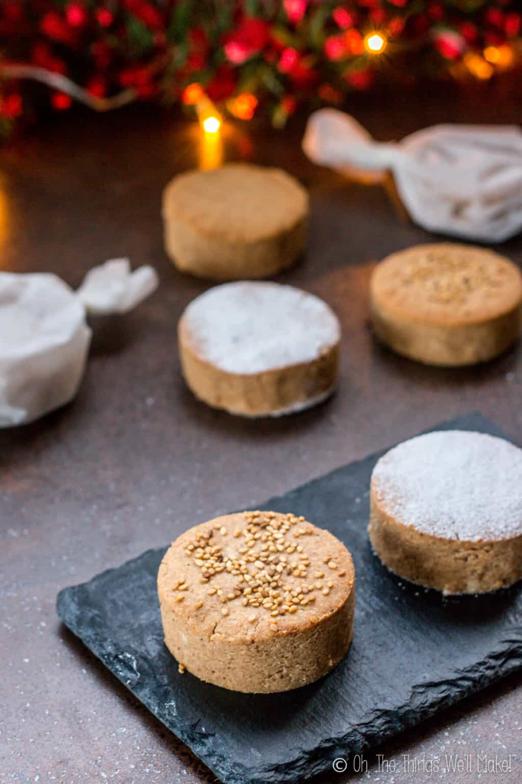 A close up of one mantecados and one polvorones cookies on a black slate platter, with other cookies on the countertop (some cookies wrapped in parchment paper.)