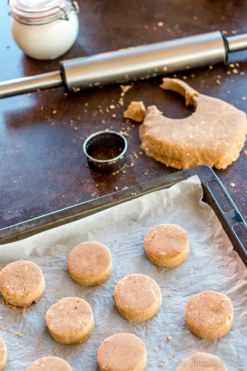 Several pieces of cut mantecados on a baking sheet. On top is a rolling pin, dough with a cut section and a circle cutter.