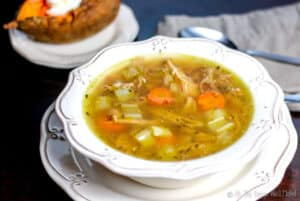 Overhead view of a turkey soup with celery, carrots, and turkey pieces in view. A baked sweet potato can be seen in the background.
