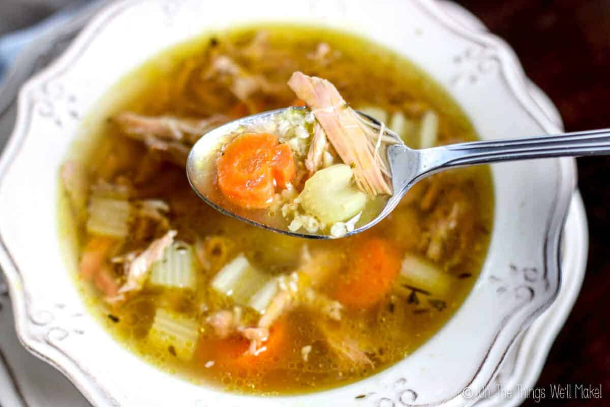 closeup view of spoon with turkey, carrot slice and celery over bowl of turkey rice soup