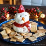 A snowman made out of cream cheese surrounded by square crackers.