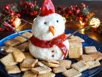 A snowman cheese ball surrounded by crackers.