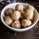 Closeup of coconut date balls in a white bowl.