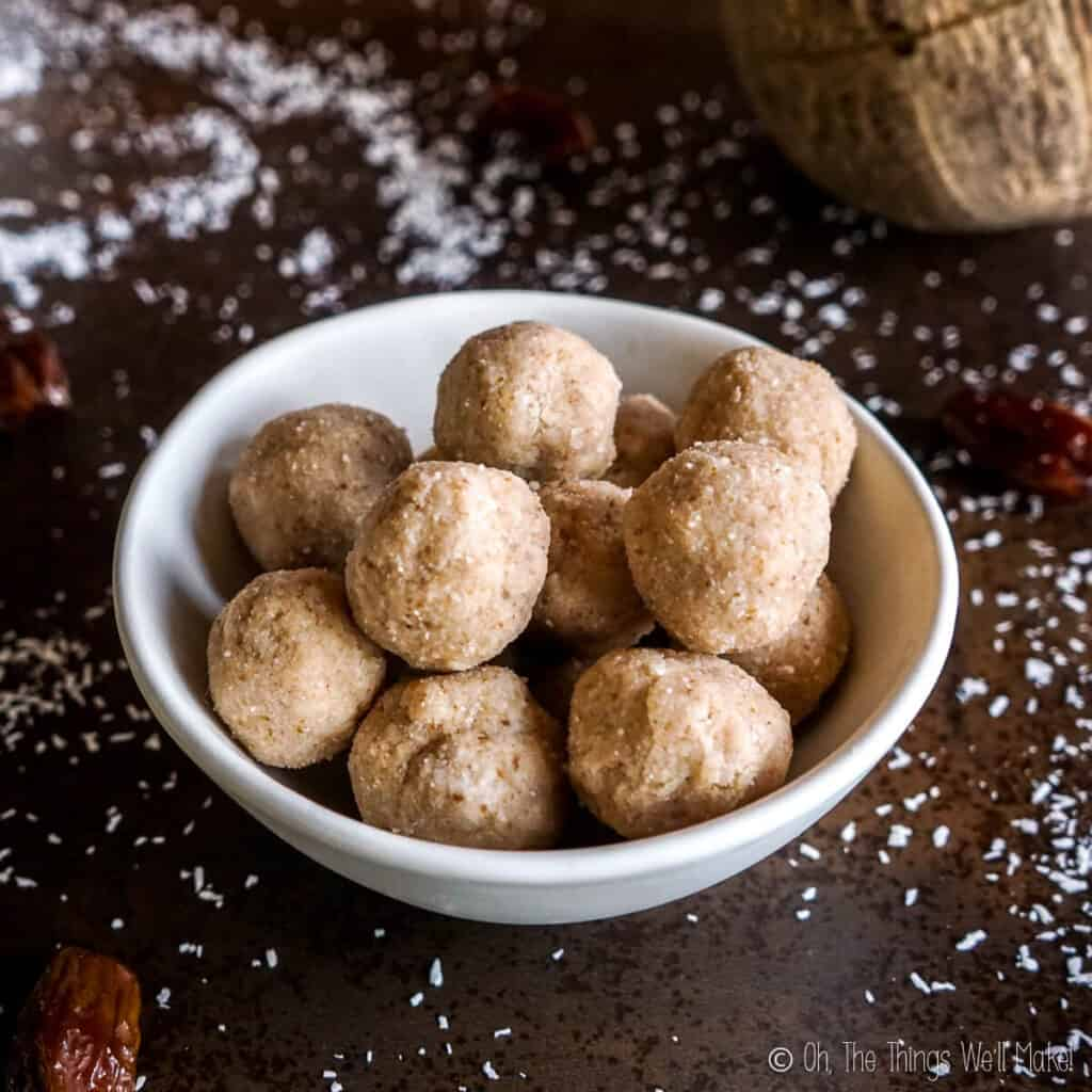 A bowl of coconut date balls surrounded by shredded coconut