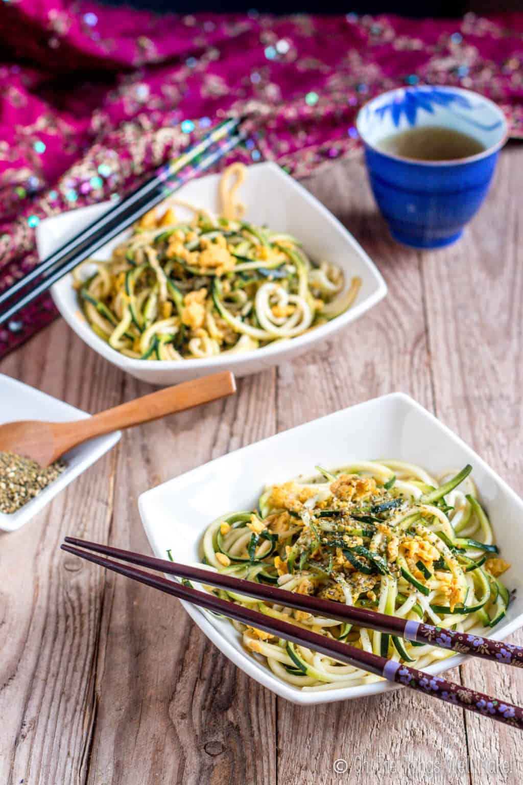 Two white square bowls filled with  pan fried zucchini noodles garnished with eggs, and have black chopsticks on the side of the bowls.
