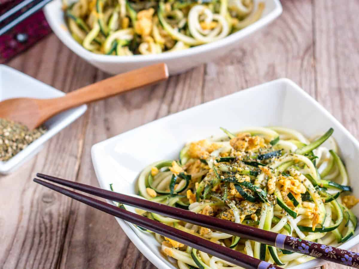 Two bowls full of homemade zucchini noodles with chopsticks on the top side of the bowls.