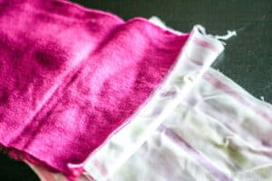 Closeup of the seam between a pink fabric and a light colored striped one as seen in the inverse side of the fabric.