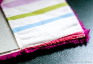 Closeup of the corner of a cloth covered notebook, showing the details of the hand-stitched edge.