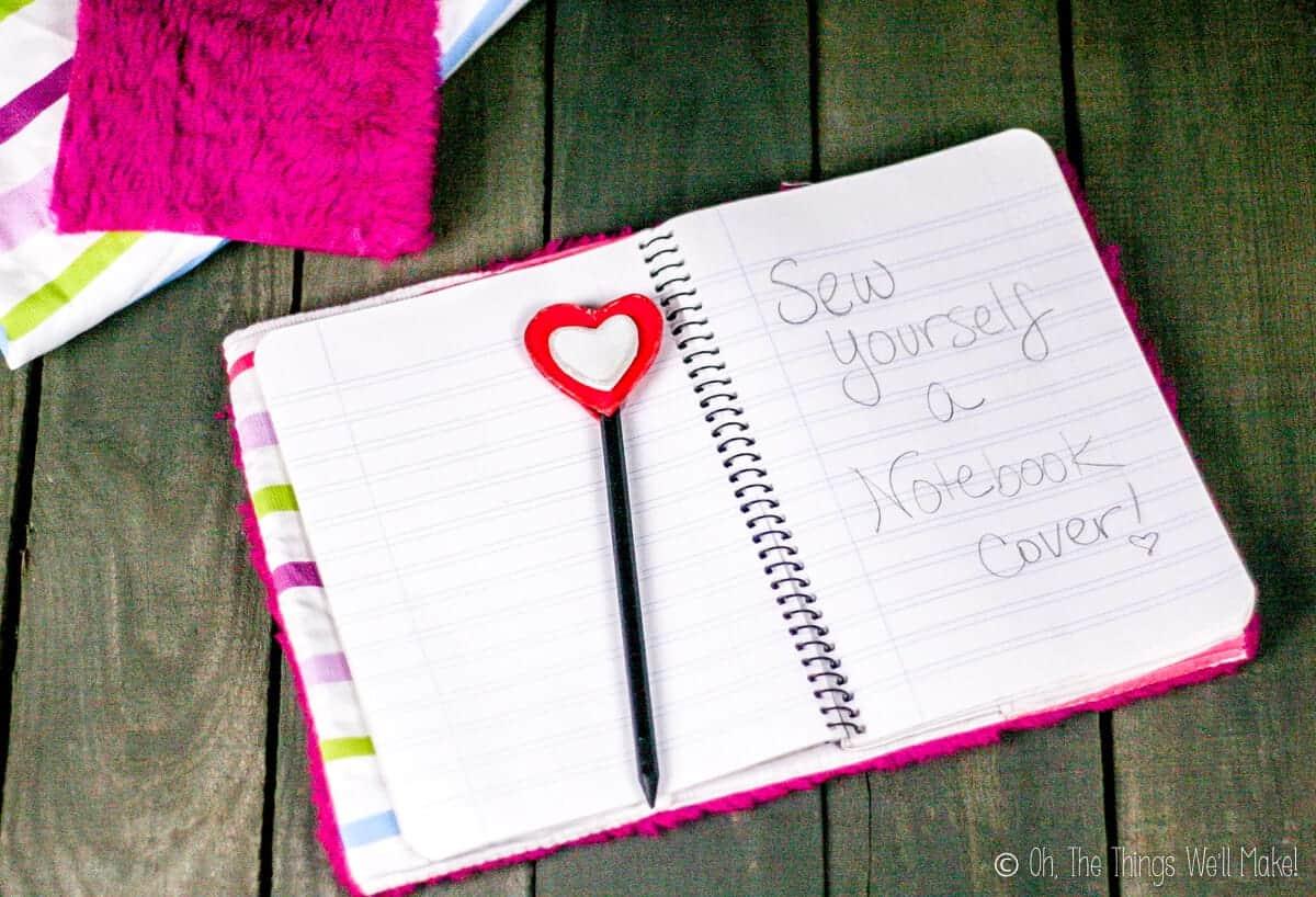 """Sew Yourself a Notebook Cover"" written on an open notebook."