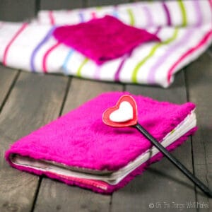 A pink fuzzy covered notebook and a pencil with foam hearts placed on a wood pallet, with pink striped cloth scraps in the background.
