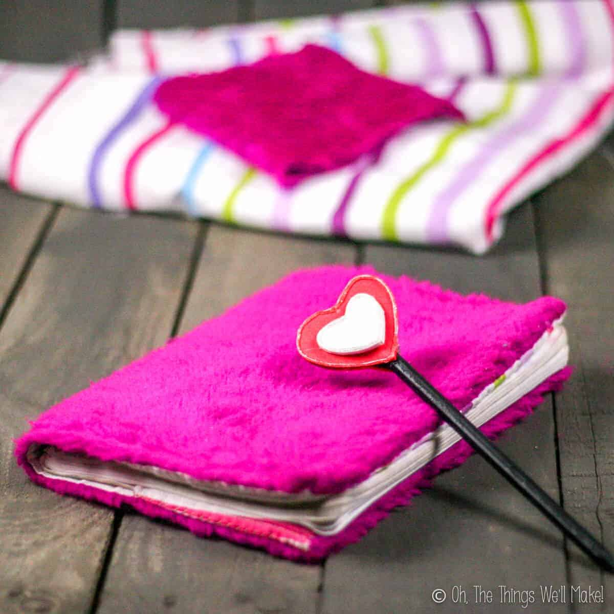 A notebook with a fuzzy pink notebook cover and a pencil with craft foam hearts both on a pallet with cloth scraps behind them.