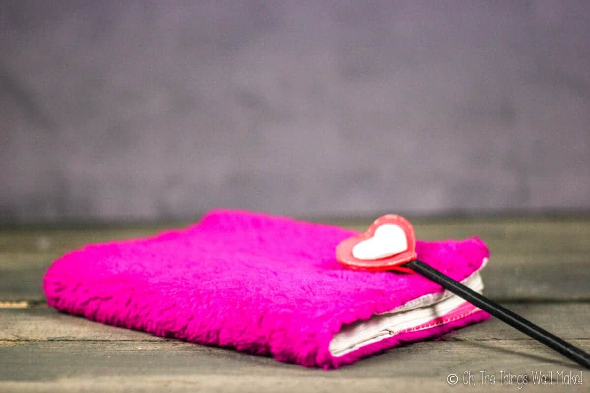 A notebook with a pink fuzzy cloth cover and a pencil with a heart shaped craft foam decoration.