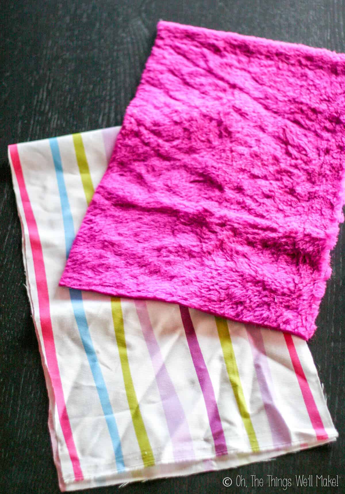 A striped fabric underneath a piece of a fuzzy pink cloth.