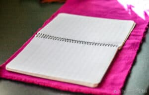 An open notebook sitting on a piece of pink cloth.