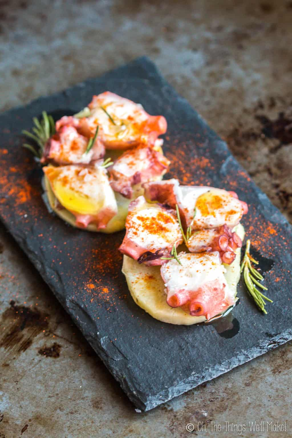 Close up top view of two servings of pulpo a la gallega, galician style octopus on a single slice of potato, placed on a black slate platter.