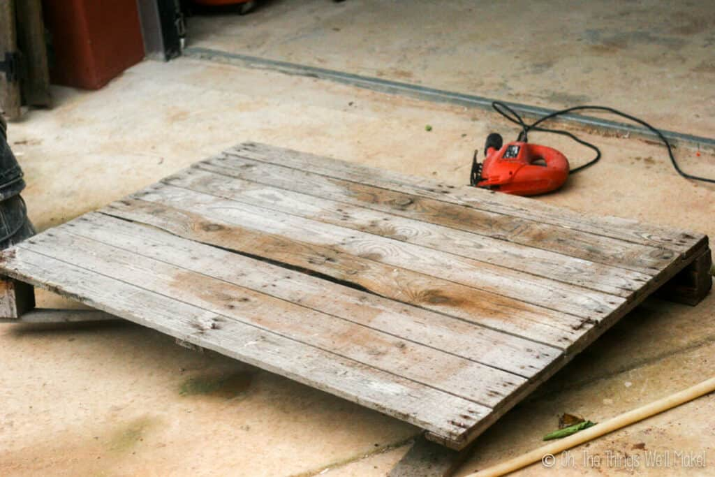 A wooden pallet on the ground with a jigsaw behind it.