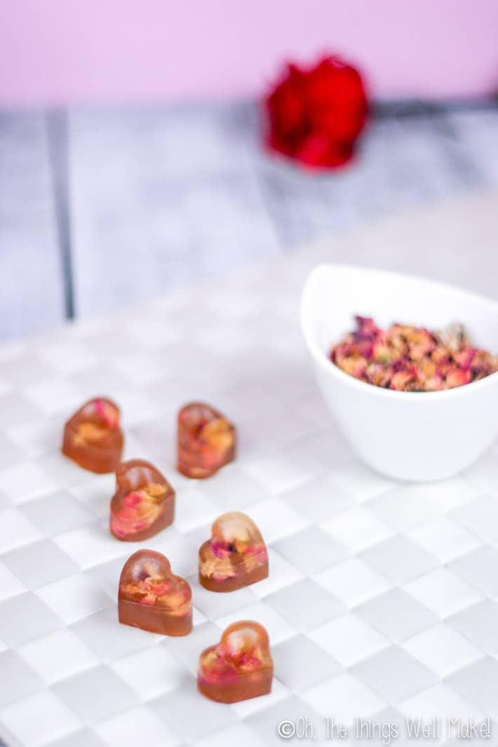 rose petal sweets next to a bowl of dried rose petals and a fresh rose.