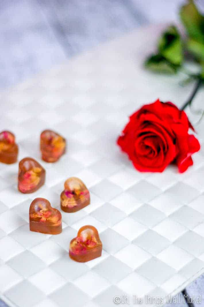 rose petal gummies along side a fresh rose