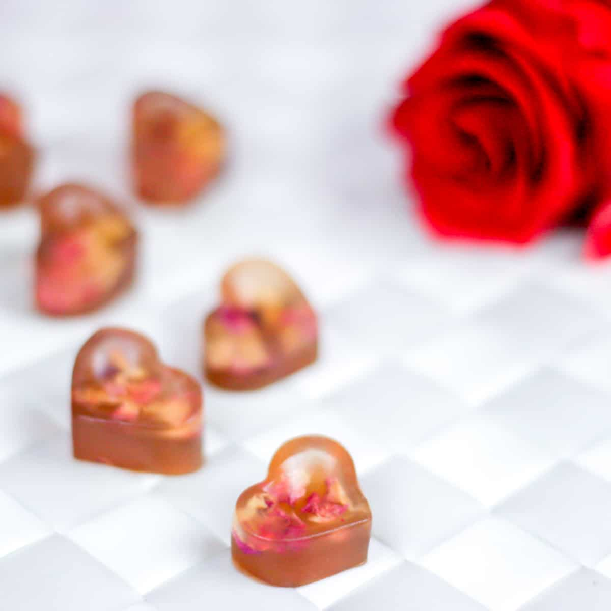 Closeup of heart-shaped gummy treats with real rose petals inside next to a red rose.