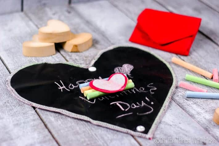 Heart chalkboard with 4 pieces of chalk and a chalkboard eraser in the center.