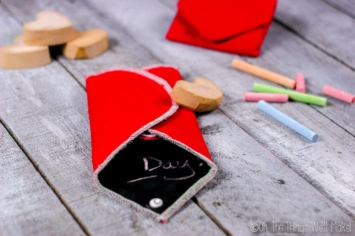 folding both sides of the heart chalkboard over the chalk and eraser.