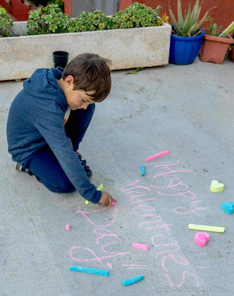 An eight year old boy playing with vibrant homemade sidewalk chalk.