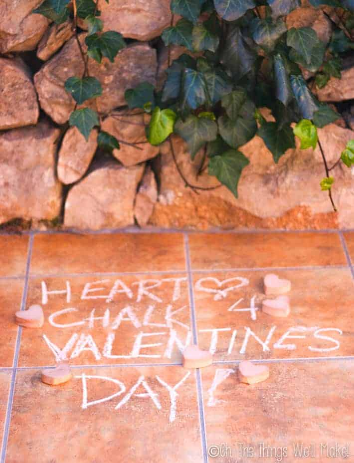 """Chalk writing on the ground saying """"Heart chalk 4 Valentine's Day"""""""