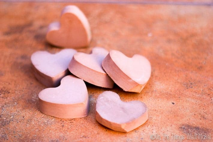 6 pieces of heart-shaped sidewalk chalk in a pile outside.