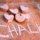 """Picture with """"I"""" written on the ground followed by several pieces of heart-shaped chalk, followed by """"chalk."""""""