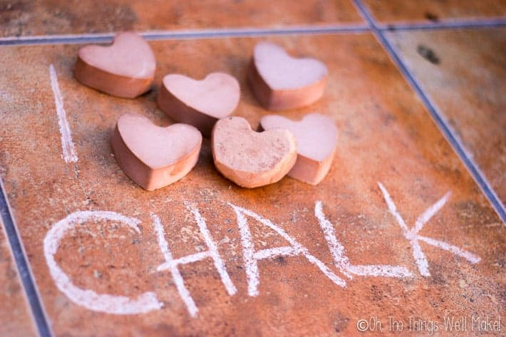 "Picture with ""I"" written on the ground followed by several pieces of heart-shaped chalk, followed by ""chalk."""